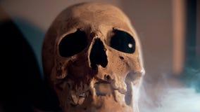 Schädel mit den blauen Augen umfasst im weißen Rauche Halloween stock footage