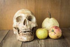 Schädel- und Brandwundenfruchtstillleben auf hölzernem Hintergrund Lizenzfreie Stockfotografie