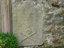 Schädel-und Kreuz-Knochenmarkierungen auf Grabstein auf Lindisfarne die heilige Insel Stockfotografie