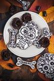Schädelplätzchen mit Lakritzblumen für Halloween Stockbilder