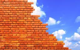 Schädigende Backsteinmauer und blauer Himmel Stockfotos