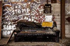 Schädigende und schmutzige Ledercouch innerhalb der industriellen Halle stockbilder