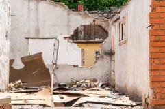 Schädigende Wand des inländischen Zivilhauses oder des Gebäudes mit dem Loch und eingestürztem Dach zerstört durch Granate im Kri stockfotografie