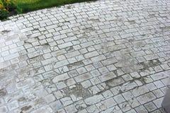 Schädigender Straßenbetoniermaschinenziegelstein in der Gartenpflasterung Lizenzfreies Stockfoto