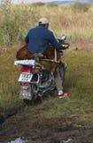 Schäfer trägt eine Ziege zum Markt des Nomaden lizenzfreie stockbilder