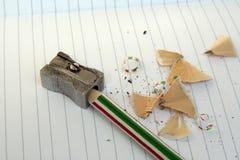 Schärfen des Bleistifts auf einem Notizbuch in den Linien Lizenzfreies Stockfoto