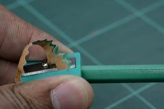 Schärfen Sie den grünen Bleistift mit dem grünen Bleistiftspitzer Lizenzfreie Stockbilder