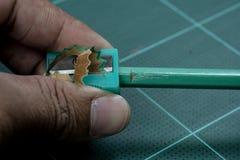 Schärfen Sie den grünen Bleistift mit dem grünen Bleistiftspitzer Lizenzfreies Stockbild