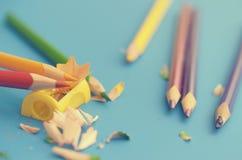 Schärfen Sie die farbigen Bleistifte mit einem Bleistiftspitzer Lizenzfreies Stockbild