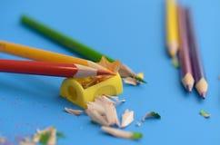 Schärfen Sie die farbigen Bleistifte mit einem Bleistiftspitzer Stockfotografie