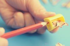 Schärfen Sie die farbigen Bleistifte mit einem Bleistiftspitzer Stockbilder