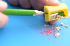 Schärfen Sie die farbigen Bleistifte mit einem Bleistiftspitzer Lizenzfreie Stockfotos