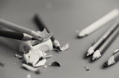 Schärfen Sie die farbigen Bleistifte mit einem Bleistiftspitzer Stockfoto