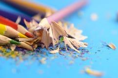 Schärfen Sie die farbigen Bleistifte mit einem Bleistiftspitzer Lizenzfreie Stockbilder