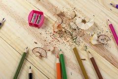 Schärfen von Farbtonbleistiften auf einem hölzernen Schreibtisch Stockfotografie