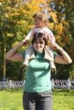 Schätzchen auf Mutterschultern lizenzfreie stockbilder