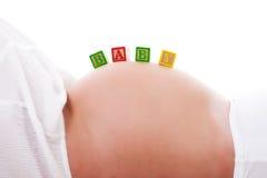 Schätzchen-Blöcke auf einem Magen der schwangeren Frau Lizenzfreies Stockbild