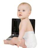 Schätzchen, das auf einem weißen Hintergrund mit Laptop sitzt Lizenzfreies Stockfoto
