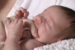 Schätzchen, das auf Finger des Mutter saugt Stockfotos