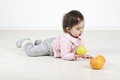 Schätzchen, das auf Fußboden mit Früchten liegt Stockbilder