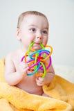 Schätzchen, das auf gelbem Tuch-Zerfressenspielzeug sitzt Stockfotos