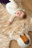 Schätzchen, das auf Tigerwolldecke spielt lizenzfreie stockfotografie