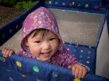Schätzchen, das draußen im Playpen lächelt Stockfotos