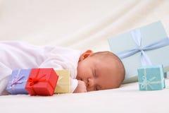 Schätzchen, das durch Geschenkboxen schläft Lizenzfreie Stockfotos