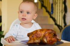 Schätzchen, das ein großes gegrilltes Huhn isst Lizenzfreie Stockfotos
