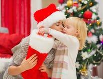 Schätzchen, das Geschenk von der Weihnachtssocke herausnimmt Stockbild