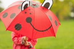 Schätzchen, das hinter rotem Regenschirm sich versteckt Stockfoto
