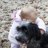 Schätzchen, das Hund umarmt. Stockfoto