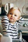 Schätzchen, das im Highchair sitzt Kind sitzt am leeren Tisch und am Wartung Ihre Fütterung Er ist blondes nettes Kleinkind in de Stockfotografie