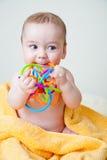 Schätzchen, das mehrfarbiges Spielzeug auf gelbem Tuch zerfrisst Lizenzfreie Stockfotografie