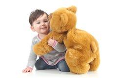 Schätzchen, das mit einem Teddybären spielt Stockfotos