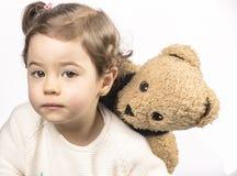 Schätzchen, das mit einem Teddybären spielt Lizenzfreies Stockfoto