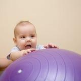 Schätzchen, das mit gymnastischer Kugel spielt. stockfoto