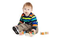 Schätzchen, das mit hölzernen Spielzeugwürfeln mit Zeichen spielt. Hölzernes Alphabet Lizenzfreies Stockfoto