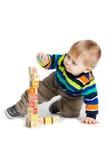 Schätzchen, das mit hölzernen Spielzeugwürfeln mit Zeichen spielt. Hölzernes Alphabet Lizenzfreie Stockfotografie