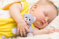 Schätzchen, das mit ihrem Bärenspielzeug schläft Stockfotos