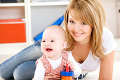 Schätzchen, das mit Spielwaren mit glücklicher Mutter spielt stockbild