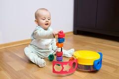 Schätzchen, das mit Spielzeug spielt Stockbilder