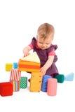 Schätzchen, das mit Spielzeugblöcken spielt Stockfotografie
