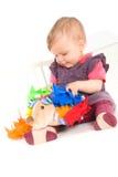 Schätzchen, das mit weichem Spielzeug spielt Stockbild
