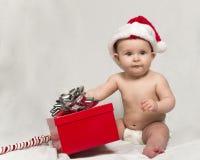 Schätzchen, das Sankt-Hut mit Weihnachtsgeschenk trägt Lizenzfreies Stockfoto