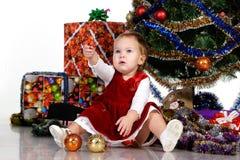 Schätzchen, das unter einem Weihnachtsbaum sitzt lizenzfreie stockfotografie