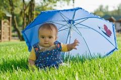 Schätzchen, das unter Regenschirm sitzt Stockfotografie