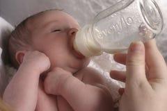 Schätzchen, das von Mother mit der Flasche gefüttert wird Stockbild