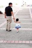 Schätzchen, das wie ein Baumuster mit ihrem Vater geht Stockfoto