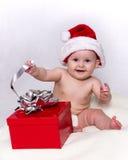 Schätzchen im Sankt-Hut, der mit Weihnachtsgeschenk spielt Lizenzfreies Stockfoto